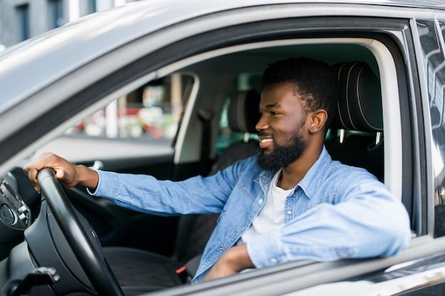 自信と誇りを持って彼の新しい高価な車を運転する若い裕福な成功した実業家
