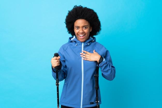 自分を指している青色の背景に分離されたバックパックとトレッキングポールを持つ若いアフリカ系アメリカ人