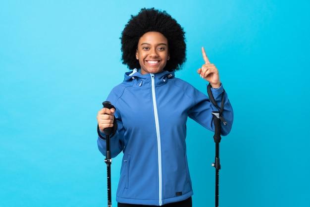 素晴らしいアイデアを指している青色の背景に分離されたバックパックとトレッキングポールを持つ若いアフリカ系アメリカ人