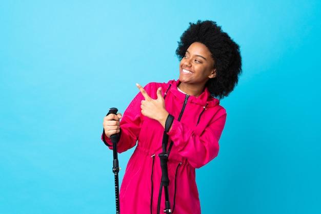 若いアフリカ系アメリカ人のバックパックとトレッキングポールが人差し指で指している青色の背景に分離された素晴らしいアイデア