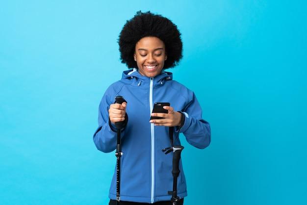 Молодой афроамериканец с рюкзаком и треккинговыми палками изолирован на синем, отправляет сообщение по мобильному телефону