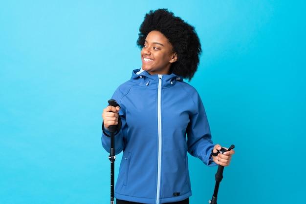 Молодой афроамериканец с рюкзаком и треккинг поляков, изолированных на синей стене, глядя в сторону и улыбается
