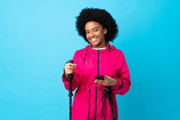 Молодой афроамериканец с рюкзаком и треккинг полюсов, изолированных на синей стене, отправив сообщение с мобильного телефона