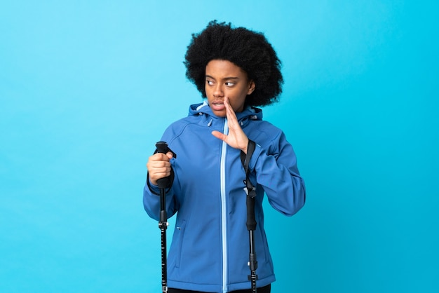 Молодой афроамериканец с рюкзаком и треккинговыми палками изолирован на синем и шепчет что-то с удивленным жестом, глядя в сторону