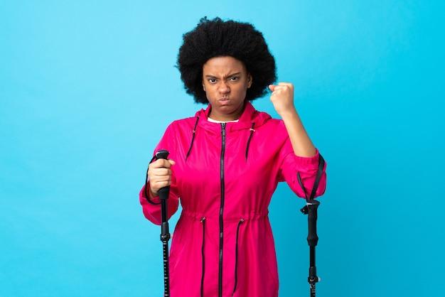 불행한 표정으로 파란색에 고립 된 배낭과 트레킹 기둥이있는 젊은 아프리카 계 미국인