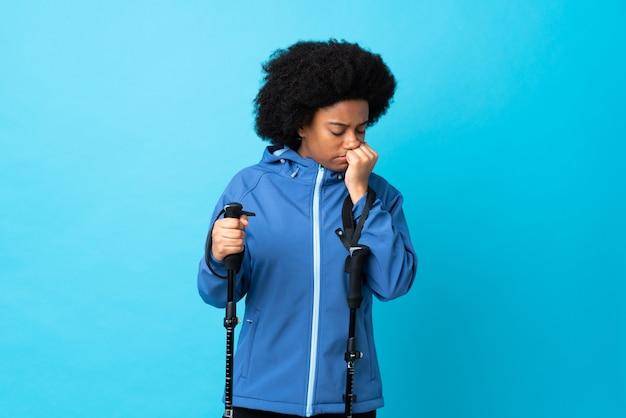 Молодой афроамериканец с рюкзаком и треккинг поляков на синей стене, имеющие сомнения