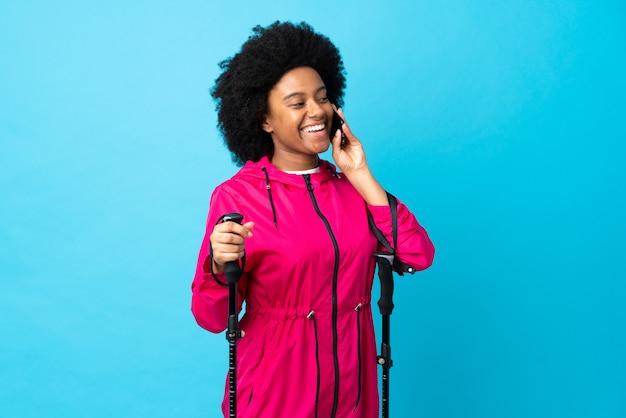 Молодой афроамериканец с рюкзаком и треккинговыми палками на синей стене ведет разговор с мобильным телефоном