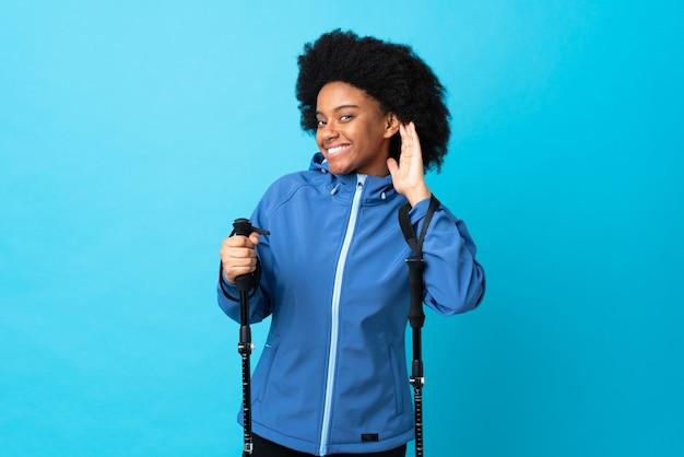 Молодой афроамериканец с рюкзаком и треккинговыми палками на синей стене слушает что-то, положив руку на ухо