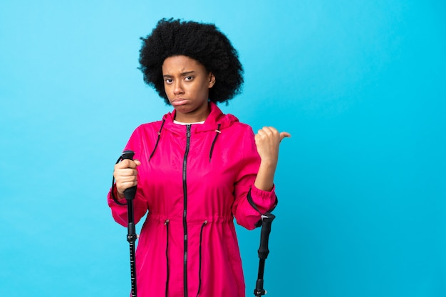 파란색 벽에 배낭과 트레킹 기둥 불행하고 측면을 가리키는 젊은 아프리카 계 미국인