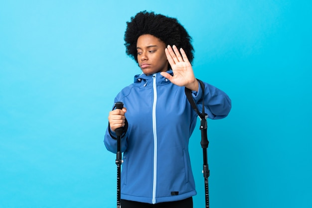 Young africa american with backpack and trekking poles isolated on blue background making stop gesture and disappointed