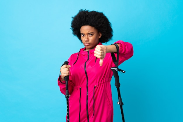 Young africa american with backpack and trekking poles isolated on blue background showing thumb down with negative expression