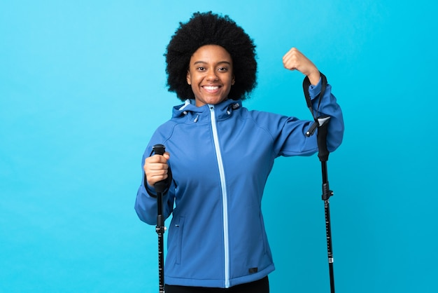 Young africa american with backpack and trekking poles isolated on blue doing strong gesture