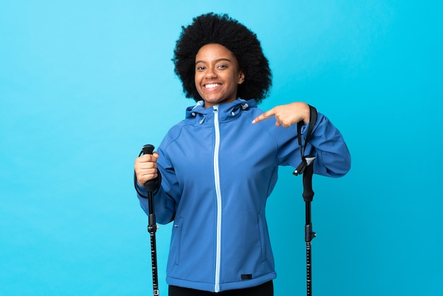 Young africa american with backpack and trekking poles isolated on blue proud and self-satisfied