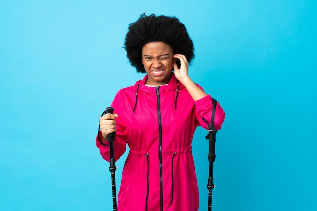 Young africa american with backpack and trekking poles isolated on blue wall frustrated and covering ears