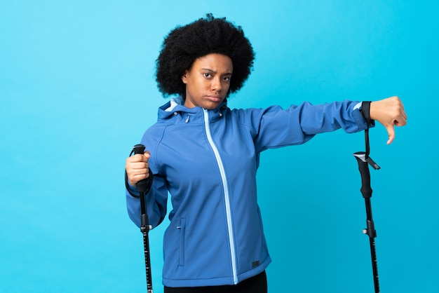 Young africa american with backpack and trekking poles isolated on blue wall showing thumb down with negative expression