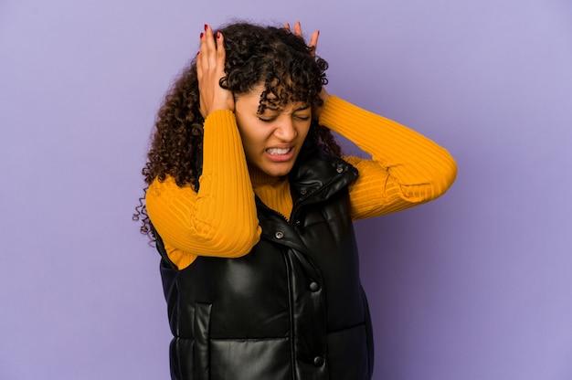 手で耳を覆う若いアフリカ系アメリカ人のアフロ女性。