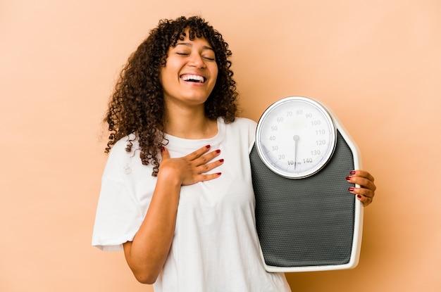 규모를 들고 젊은 아프리카 계 미국인 아프리카 여자 큰 소리로 가슴에 손을 유지 웃음.