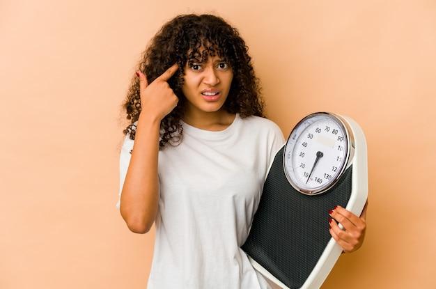 집게 손가락으로 실망 제스처를 보여주는 규모를 들고 젊은 아프리카 계 미국인 아프리카 여자.