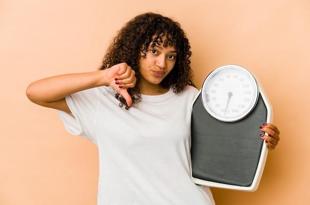 싫어하는 제스처, 엄지 손가락을 보여주는 규모를 들고 젊은 아프리카 계 미국인 아프리카 여자. 불일치 개념.