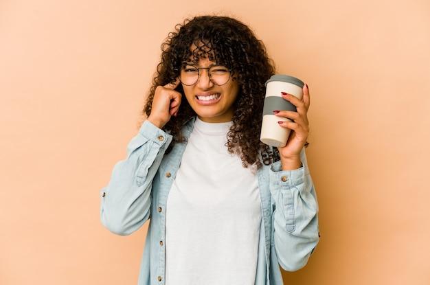 Молодая афро-американских афро женщина, держащая на вынос кофе, закрывающие уши руками.