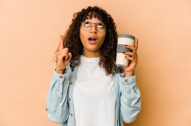 열린 된 입으로 거꾸로 가리키는 테이크 아웃 커피를 들고 젊은 아프리카 계 미국인 아프리카 여자.