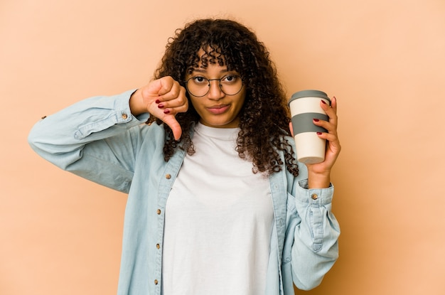 싫어하는 제스처, 엄지 손가락을 보여주는 테이크 아웃 커피를 들고 젊은 아프리카 계 미국인 아프리카 여자. 불일치 개념.
