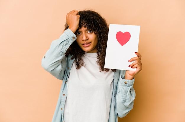 Молодая афро-американская афро-женщина, держащая в шоке открытку на день святого валентина, вспомнила важную встречу.