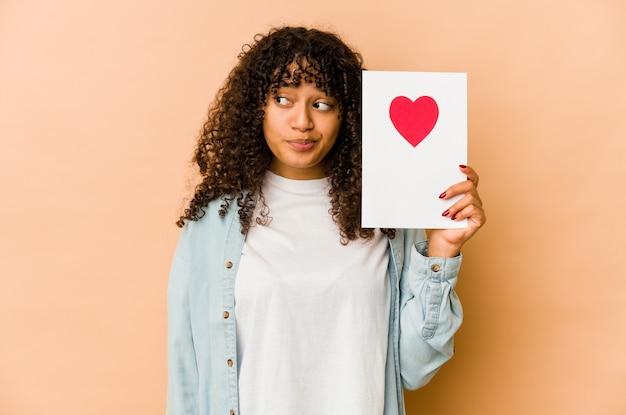 Молодая афро-американская афро-женщина, держащая карточку дня святого валентина, смущена, чувствует себя сомнительной и неуверенной.