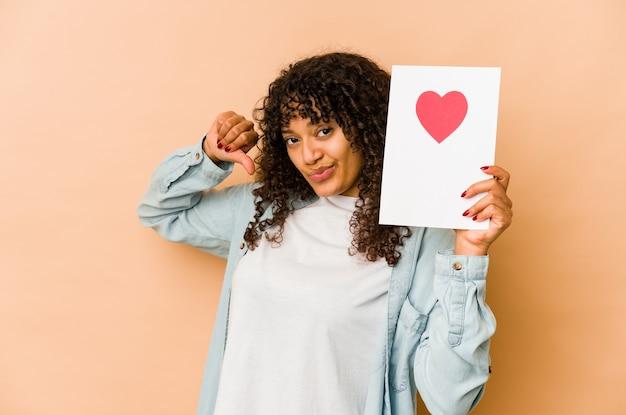 Молодая афро-американская афро-женщина, держащая открытку на день святого валентина, чувствует себя гордой и уверенной в себе, примером для подражания.