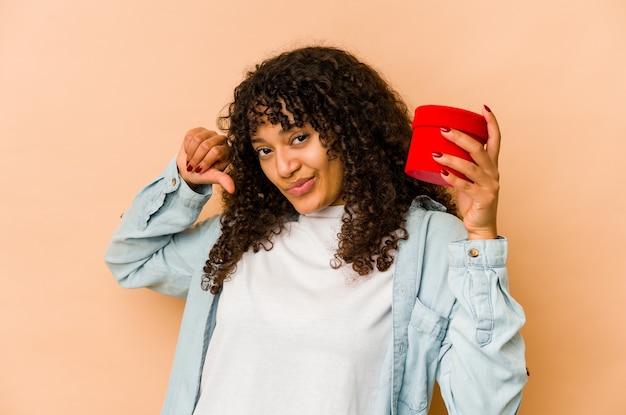 Молодая афроамериканская афро-женщина, держащая подарок на день святого валентина, чувствует гордость и уверенность в себе, пример для подражания.