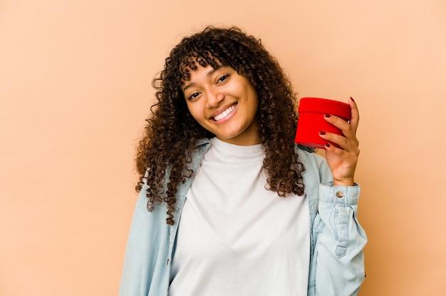 행복 하 고 웃 고 쾌활 한 발렌타인 데이 선물을 들고 젊은 아프리카 계 미국인 아프리카 여자.