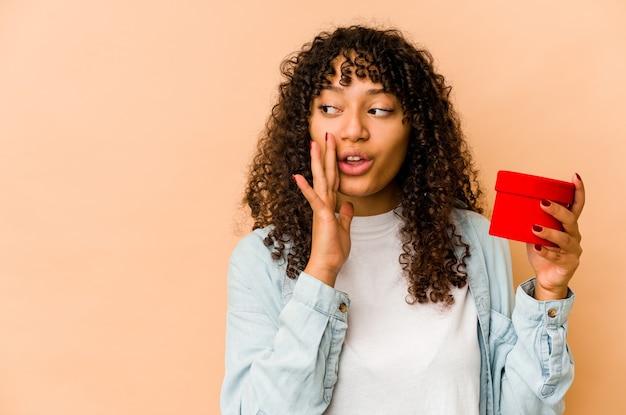 발렌타인 데이 선물을 들고 젊은 아프리카 계 미국인 아프리카 여자는 비밀 뜨거운 제동 뉴스를 말하고 옆으로보고있다
