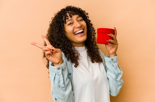 손가락으로 평화의 상징을 보여주는 즐겁고 평온한 발렌타인 데이 선물을 들고 젊은 아프리카 계 미국인 아프리카 여자.