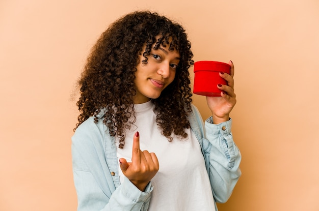 초대하는 것처럼 당신에 손가락으로 가리키는 발렌타인 데이 선물을 들고 젊은 아프리카 계 미국인 아프리카 여자 가까이와.