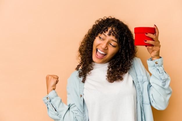 승리, 승자 개념 후 주먹을 올리는 발렌타인 데이 선물을 들고 젊은 아프리카 계 미국인 아프리카 여자.