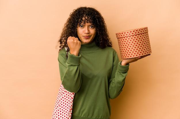 카메라, 공격적인 표정에 주먹을 보여주는 발렌타인 데이 선물을 들고 젊은 아프리카 계 미국인 아프리카 여자.