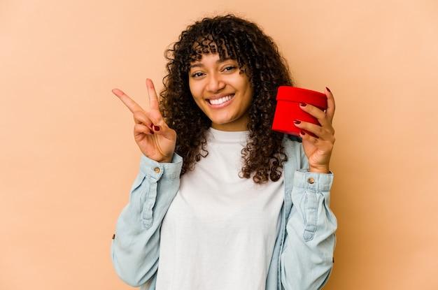 손가락으로 2 번을 보여주는 발렌타인 데이 선물을 들고 젊은 아프리카 계 미국인 아프리카 여자.