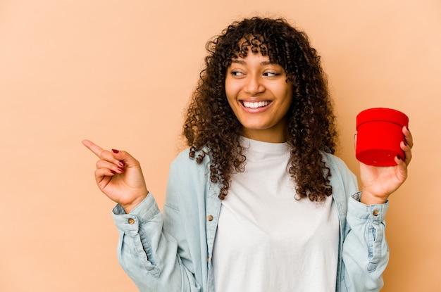 웃 고 옆으로 가리키는, 빈 공간에 뭔가 보여주는 발렌타인 데이 선물을 들고 젊은 아프리카 계 미국인 아프리카 여자.
