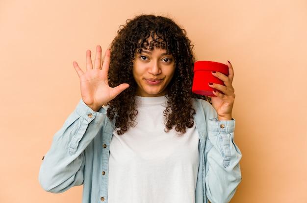 손가락으로 명랑 게재 번호 5 웃 고 발렌타인 데이 선물을 들고 젊은 아프리카 계 미국인 아프리카 여자.