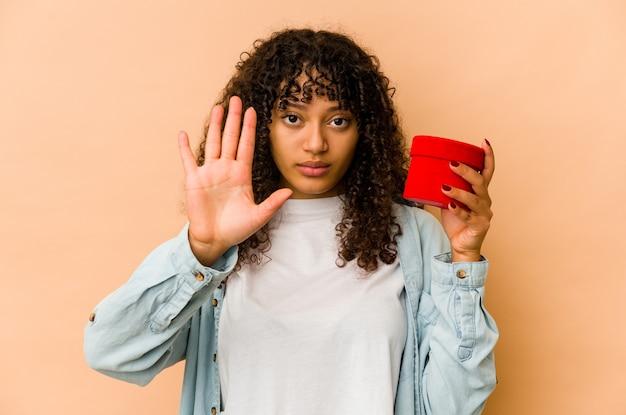 당신을 방지하는 정지 신호를 보여주는 뻗은 손으로 서 발렌타인 데이 선물을 들고 젊은 아프리카 계 미국인 아프리카 여자.