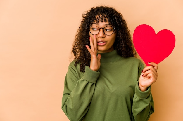 バレンタインデーの心を持っている若いアフリカ系アメリカ人のアフロ女性は秘密のホットブレーキニュースを言って脇を見ています