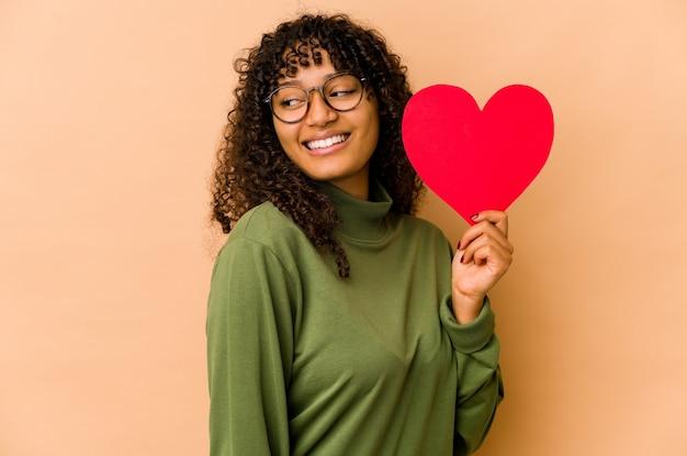 발렌타인 하트를 들고 젊은 아프리카 계 미국인 아프리카 여자는 옆으로 웃 고, 명랑 하 고 즐거운 보인다.