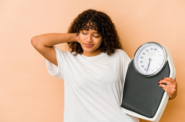 Young african american afro woman holding a scale touching back of head, thinking and making a choice.