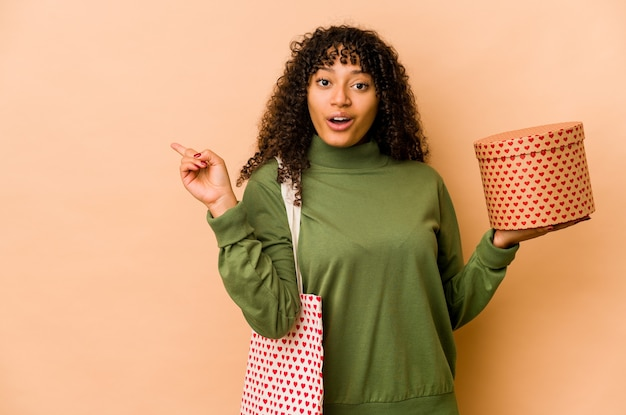 Young african american afro woman holding a valentines day gift pointing to the side