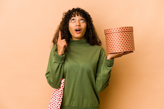 Young african american afro woman holding a valentines day gift pointing upside with opened mouth.