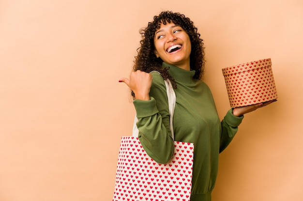 Young african american afro woman holding a valentines day gift points with thumb finger away, laughing and carefree.
