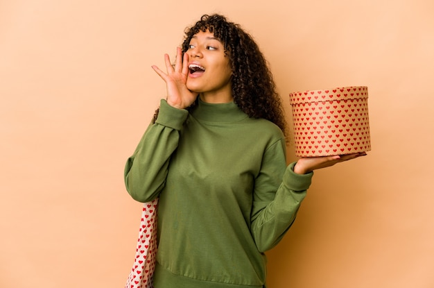 Young african american afro woman holding a valentines day gift shouting and holding palm near opened mouth.