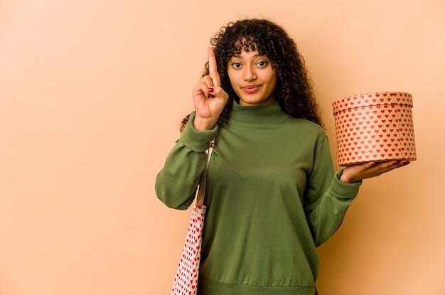 Young african american afro woman holding a valentines day gift showing number one with finger.