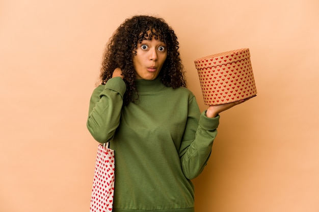 Young african american afro woman holding a valentines day gift shrugs shoulders and open eyes confused.