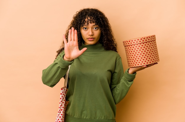 Young african american afro woman holding a valentines day gift standing with outstretched hand showing stop sign, preventing you.